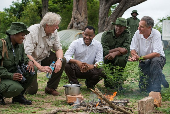 German Ambassador Egon Kochanke (second from left), Minister for Natural Resources & Tourism Lazaro Nyalandu (center), and U.S. Ambassador Mark Childress (right) talk with Tanzanian game scouts in the Selous Game Reserve.