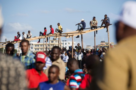 People climb up on a structure for a better view of a political rally last month. Photo: Daniel Hayduk