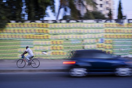 A man cycles past posters for ruling party Chama Cha Mapinduzi (CCM) presidential candidate John Magufuli and parliamentary candidate Hassan Zungu in Dar es Salaam, Tanzania. Photo: Daniel Hayduk