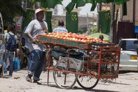 A fruit vendor walks in Kariakoo on October 29. In addition to cholera, cases of diarrheal disease are being reported. Fresh fruits and vegetables should be washed with clean water. Photo: Daniel Hayduk