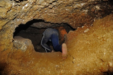 A man crawls through an artisanal gold mine. Five miners were rescued in Kahama district after surviving 40 days trapped in a mine. Photo: Daniel Hayduk