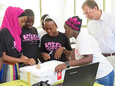 Deputy Public Affairs Officer David Feldmann listens to a group of She Codes for Change participants demonstrate a model 'smart house.' Photo: US Embassy Dar es Salaam