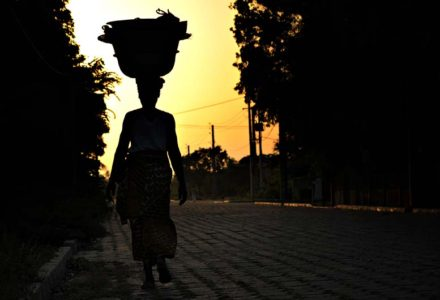 A woman passes down a street with her business on her head.