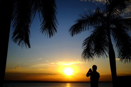 A man photographs sunset over the Indian Ocean on July 24 in Dar es Salaam, Tanzania. Photo by Daniel Hayduk