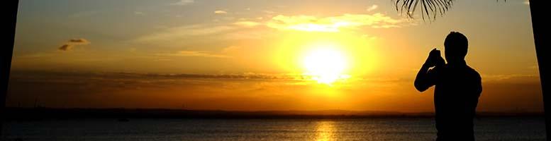 DAR ES SALAAM, TANZANIA - 13-07-24 - A man photographs sunset over the Indian Ocean on July 24 in Dar es Salaam, Tanzania. Photo by Daniel Hayduk